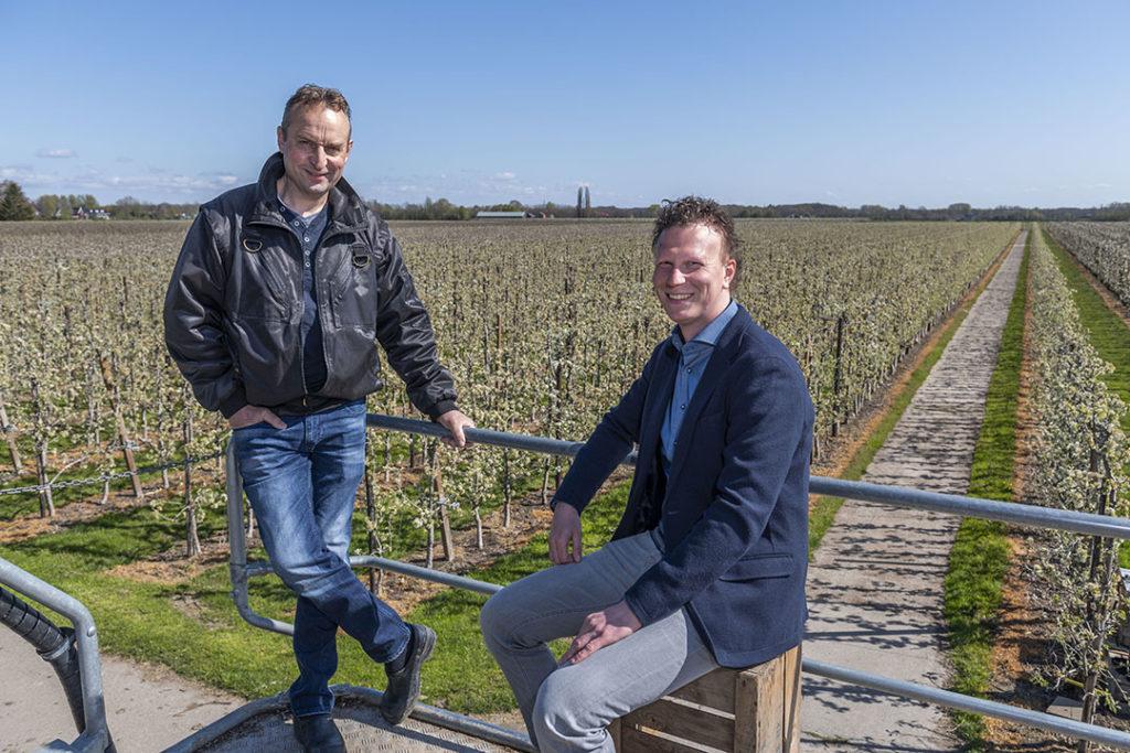 Fruitteler Gertjan Oskam (l) en NVM Agrarisch & Landelijk-taxateur Marc den Hartog overzien de bloeiende boomgaard vanaf een hoogwerker. - Foto: NVM