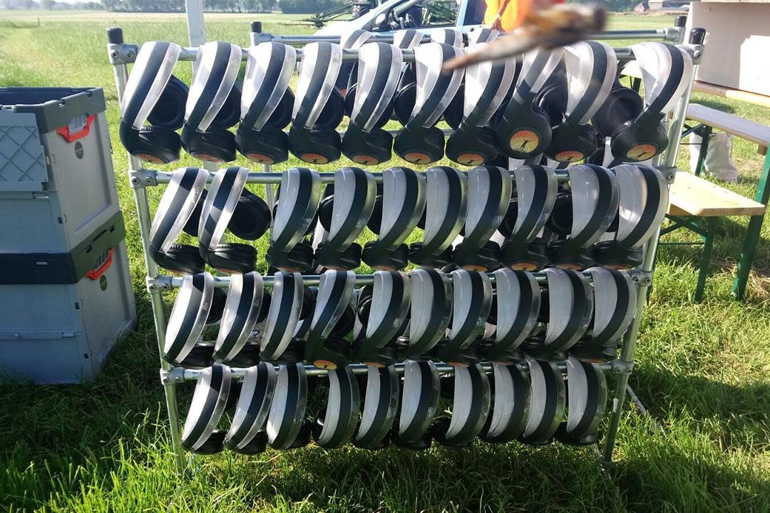Koptelefoons hangen op een rij klaar voor de bezoekers, zodat zij alle presentaties kunen volgen.