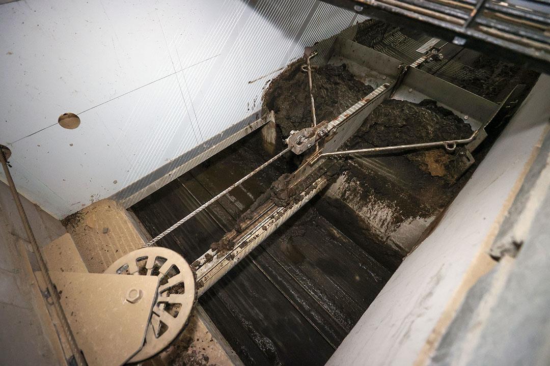 De schuif trekt de mest in de dwarsafvoer die een halve meter dieper ligt dan de put. Een schuif brengt het vervolgens uit de stal.