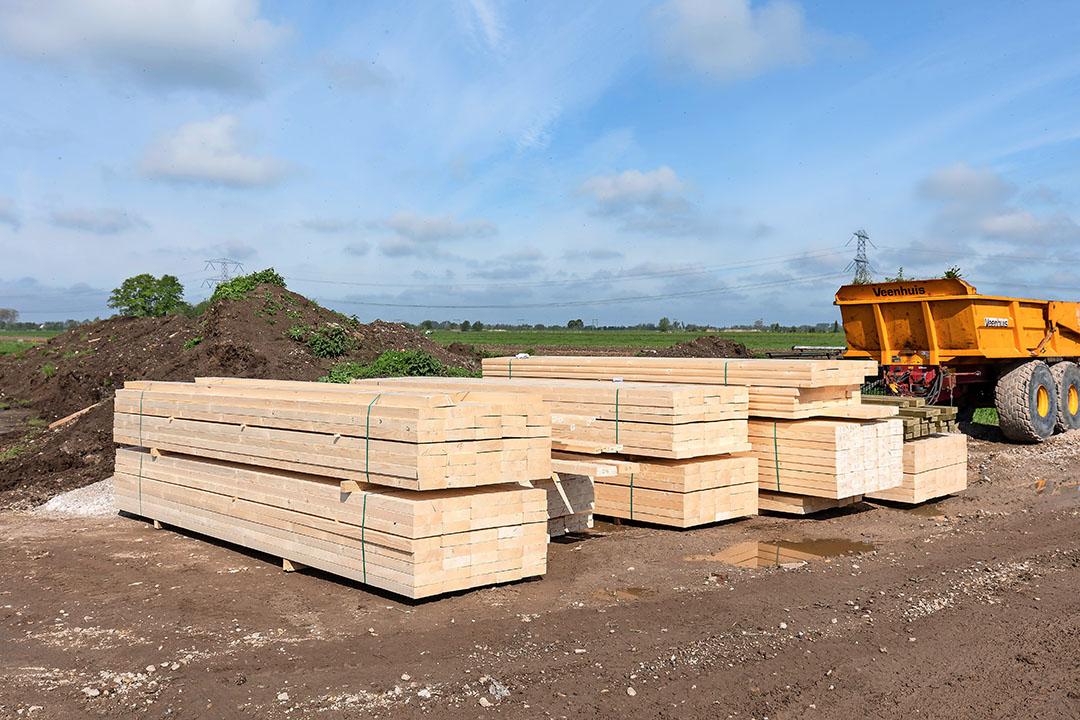 Stapels hout liggen klaar voor de bouw van de nieuwe geitenstal van familie Olsthoorn. Volgens Huisman Gemert zijn vurenhouten balken zeker 100% in prijs gestegen sinds de start van dit jaar.